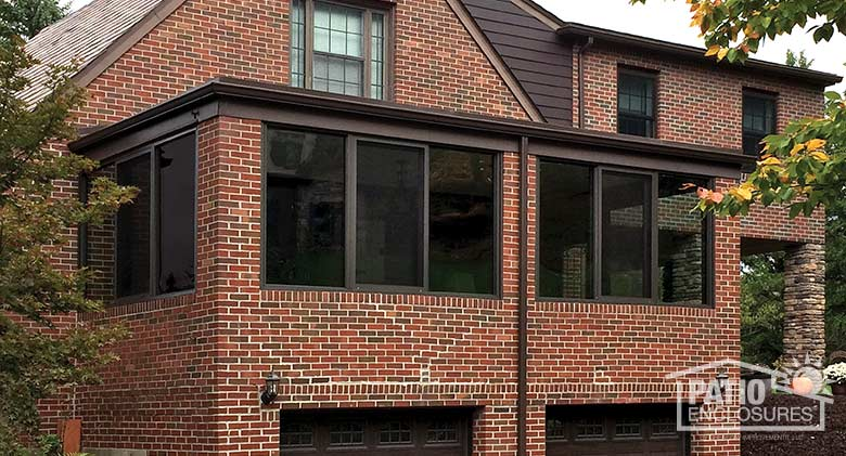 Bronze four season sunroom with aluminum frame enclosing an existing over-the-garage porch.
