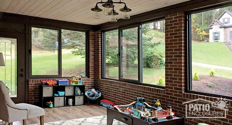 Interior of bronze four season sunroom with aluminum frame enclosing an existing over-the-garage porch.