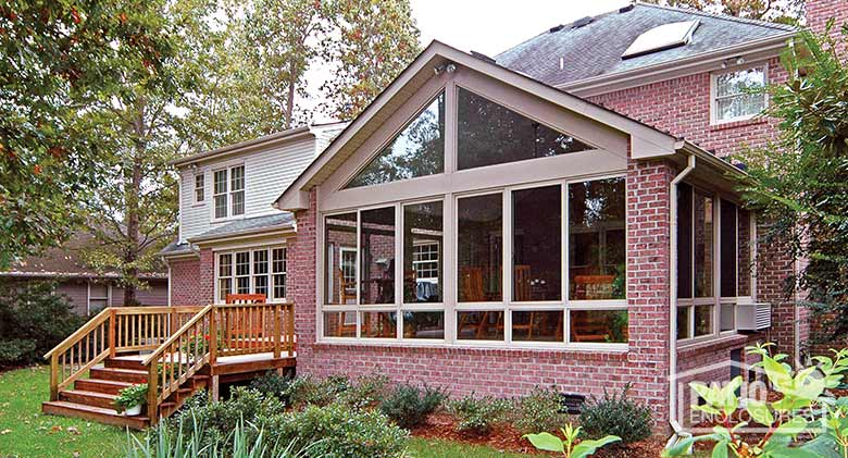 Sandstone four season sunroom with aluminum frame and glass knee wall enclosing an existing covered porch.