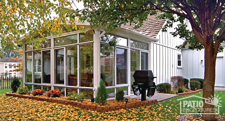 White four season sunroom with aluminum frame, glass knee wall, transom and gable roof.