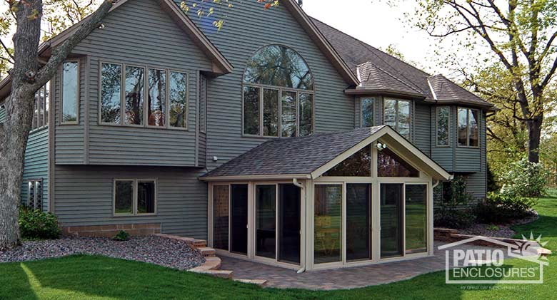 Sandstone all season sunroom with vinyl frame and shingled, gable roof.