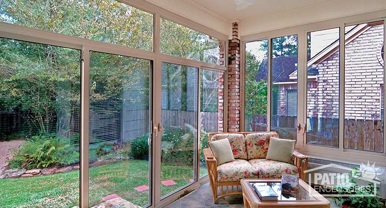 Sandstone four season sunroom with aluminum frame enclosing an existing covered patio.