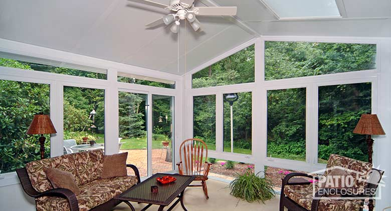 White four season sunroom with vinyl frame, glass knee wall and gable roof with glass roof panels.