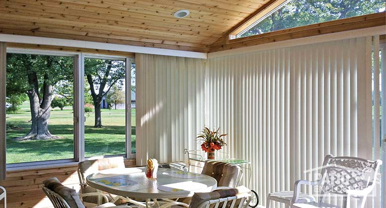 White four season sunroom with aluminum frame, solid knee wall, gable roof and custom woodwork on walls and ceiling.