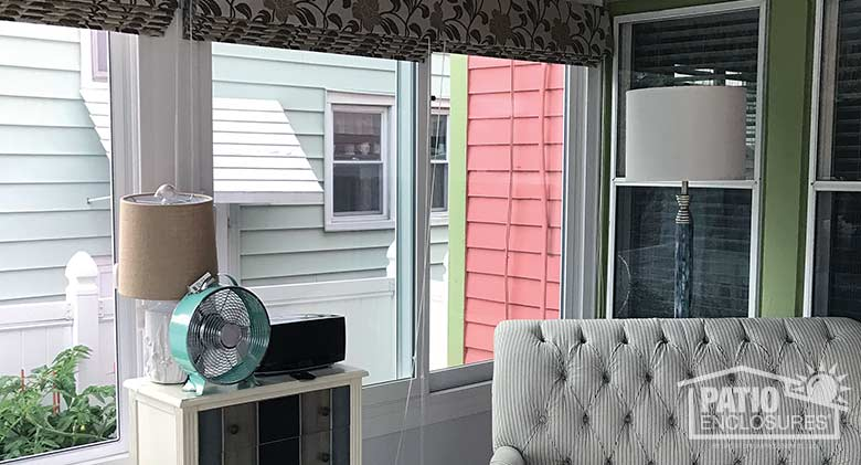 White four season sunroom with vinyl frame, solid knee wall and single-slope roof.