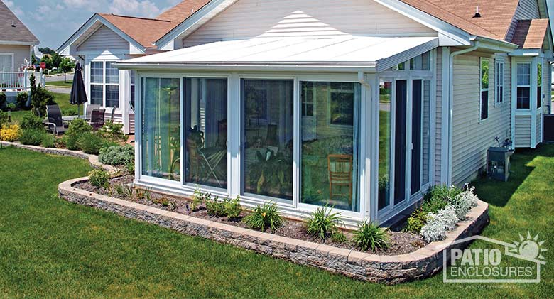 White four season sunroom with vinyl frame and single-slope roof.