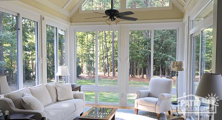 White four season sunroom with vinyl frame and glass knee wall enclosing an existing screened-in porch