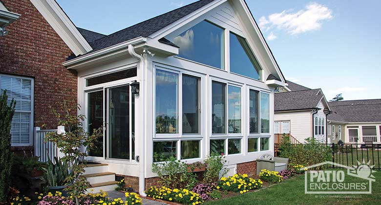 White four season sunroom with vinyl frame, glass knee wall and gable roof.