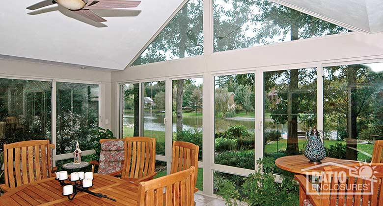 White all season sunroom with aluminum frame, glass knee wall and gable roof.