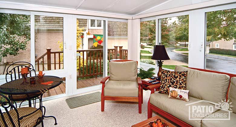 White all season sunroom with vinyl frame and single-slope roof.