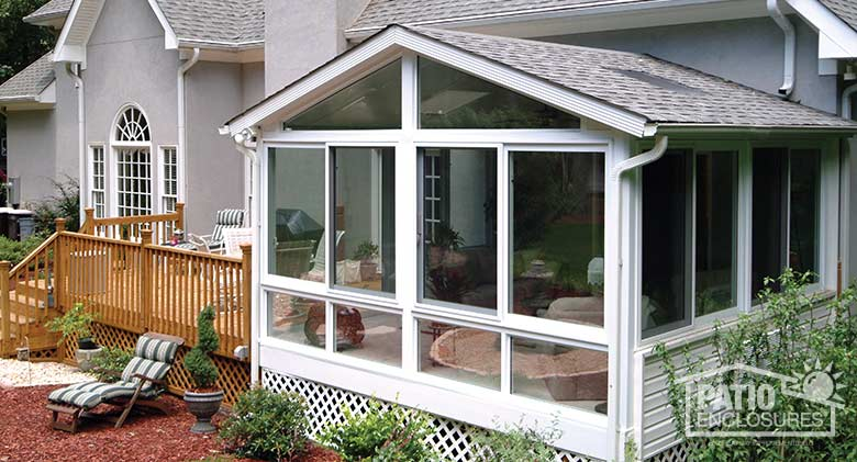 White all season sunroom with vinyl frame and gable roof with glass roof panels.