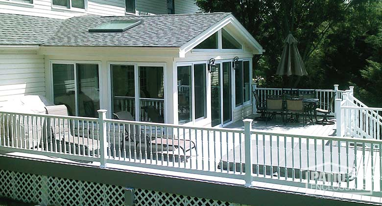 White all season sunroom with vinyl frame and gable roof.