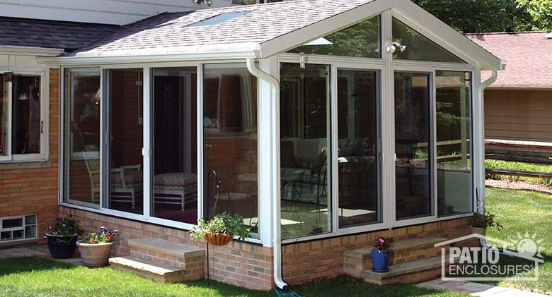 White all season sunroom with aluminum frame and glass roof panels.