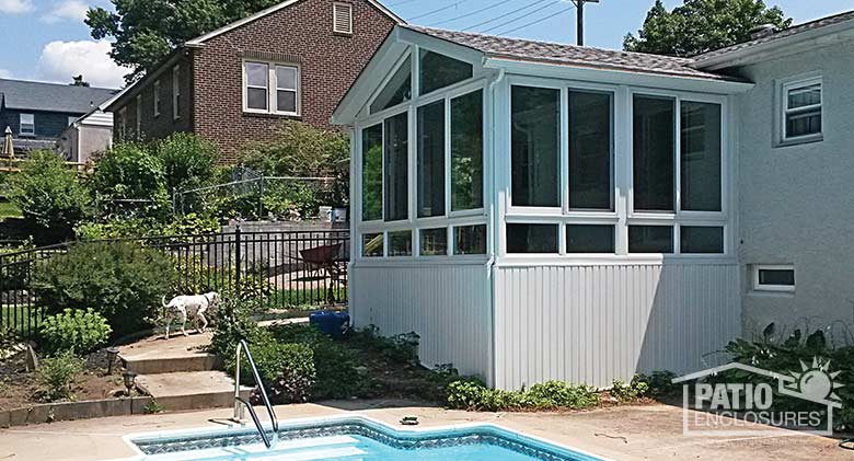 White all season sunroom with vinyl frame and shingled gable roof.