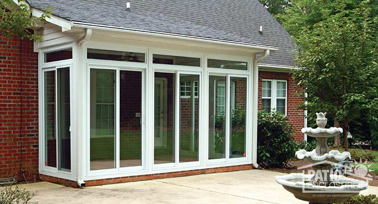 White all season sunroom with vinyl frame and transom enclosing an existing covered patio.
