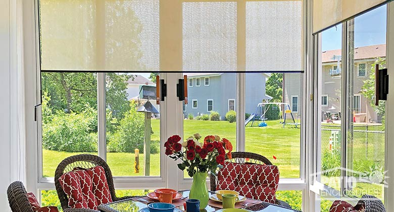 Ivory roller shades complement a contemporary dining table.