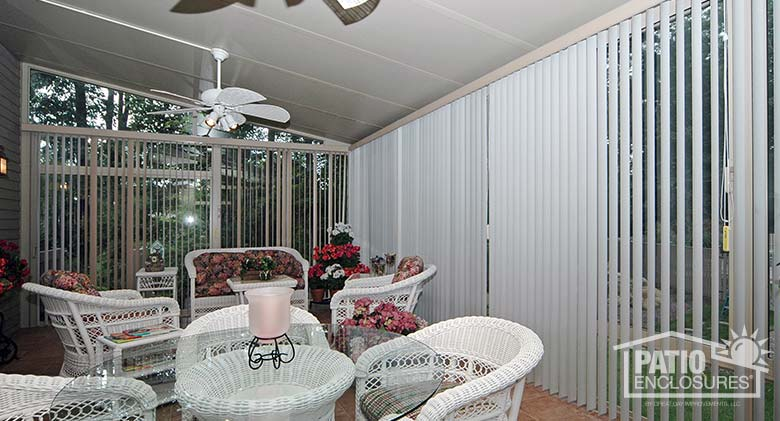 White vertical blinds in a sunroom with a single-slope roof.