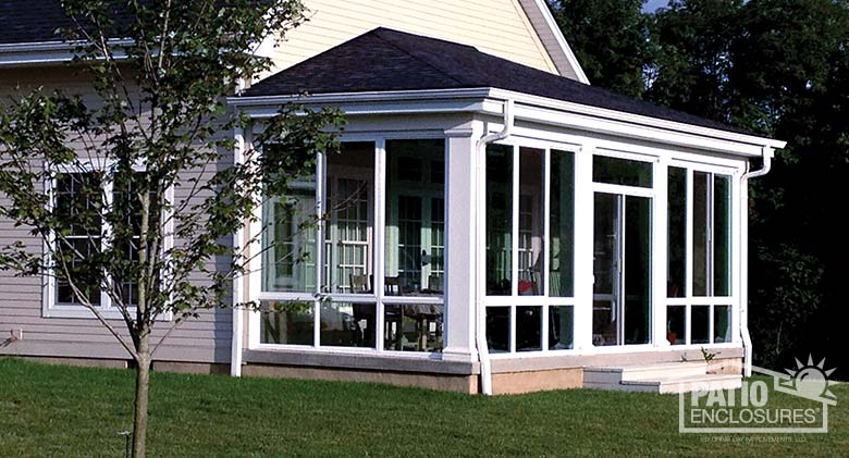 Elite three season room in white with insulated glass enclosing an existing covered back porch.