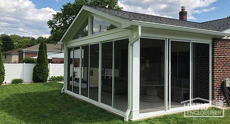 Screen room in white enclosing an existing covered patio with gable roof.