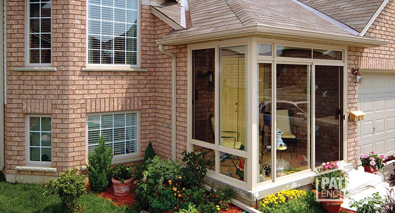 Three season room in sandstone with glass knee wall and transom enclosing an existing front porch.