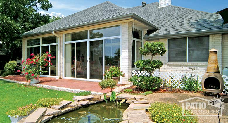 Three season room in white with insulated glass and transom enclosing an existing covered patio.
