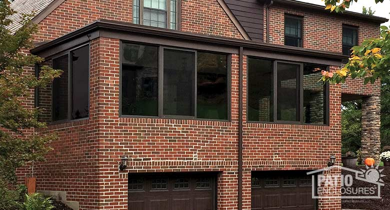 Four season room in bronze with aluminum frame enclosing an existing front porch.