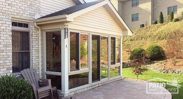 Four season room in sandstone with vinyl frame and glass knee wall enclosing an existing covered patio.