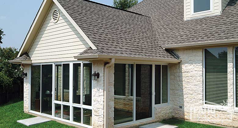 Elite three season room in white with insulated glass enclosing an existing covered porch.