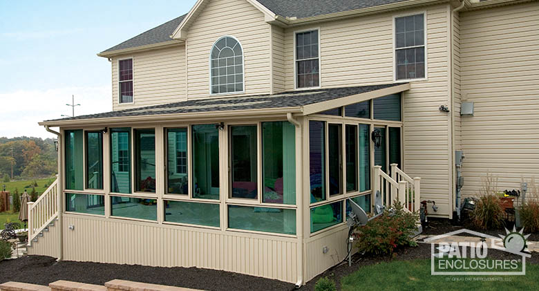 Four season aluminum sunroom in sandstone with shingled, single-slope roof, glass wings and solid knee wall with Azuria tint on glass