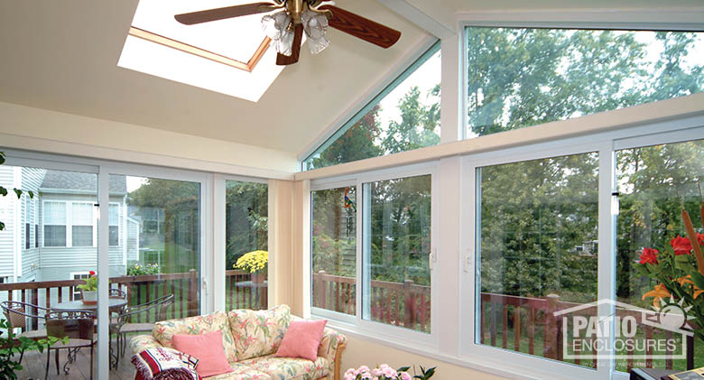 White four season vinyl sunroom with glass roof panels in gable roof, glass wings and solid knee wall