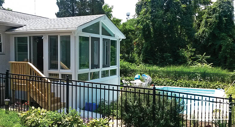 Four season vinyl sunroom in white with gable roof, glass wings, and glass knee wall