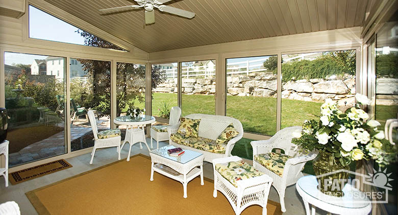 Four season vinyl sunroom in sandstone with glass wings in single-slope roof and glass knee wall