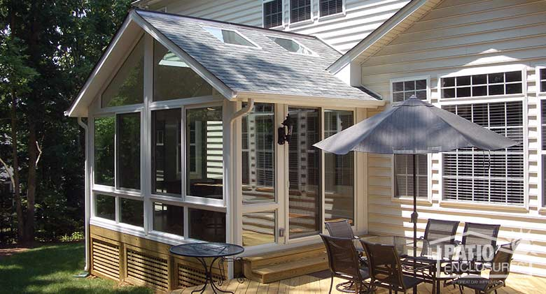 White four season sunroom with vinyl frame, glass knee walls, glass roof panels and shingled gable roof.