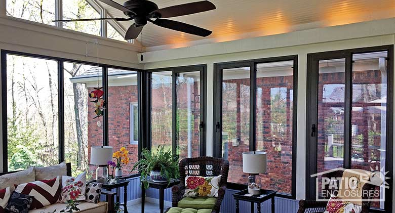 Bronze four season sunroom with aluminum frame enclosing existing covered porch.