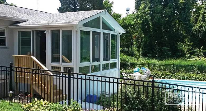White four season sunroom with vinyl frame, glass knee walls and shingled gable roof.