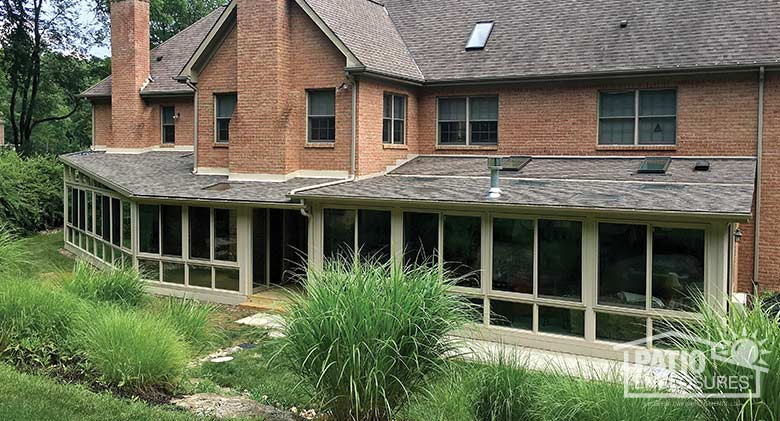 Two sandstone four season rooms with vinyl frames, glass knee walls and shingled, single-sloped roofs.
