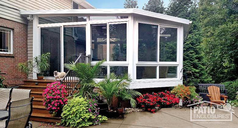 White four season sunroom in an unusual shape with vinyl frame, glass knee walls and single-slope roof.