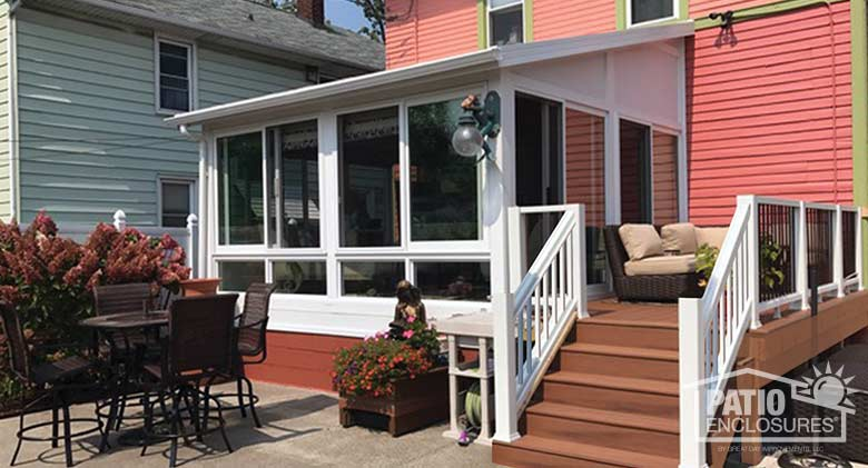 White four season sunroom with vinyl frame, glass knee walls and single-slope roof.