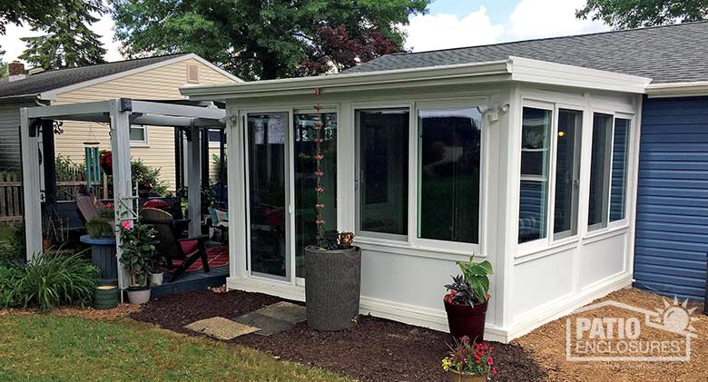 White four season room with vinyl frame, solid knee walls and single-sloped roof.