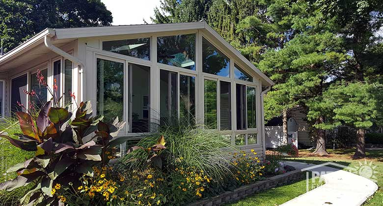 Sandstone four season sunroom with vinyl frame, glass knee wall and gable roof.