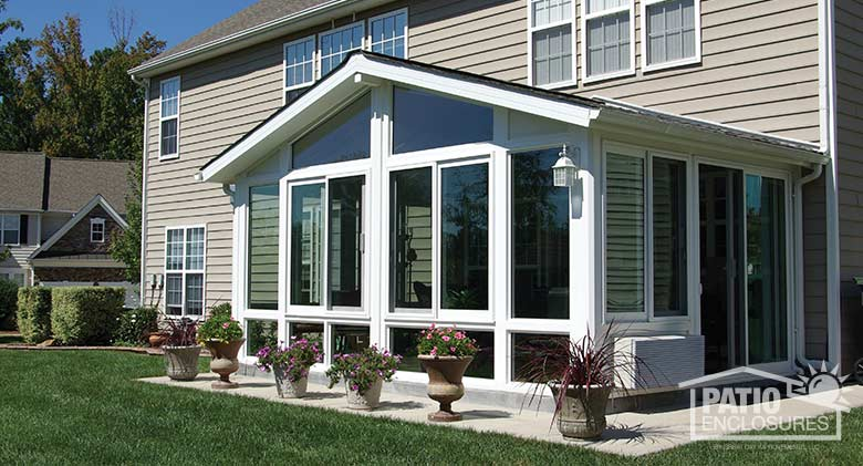White four season sunroom with vinyl frame, glass knee walls and shingled, gable roof.