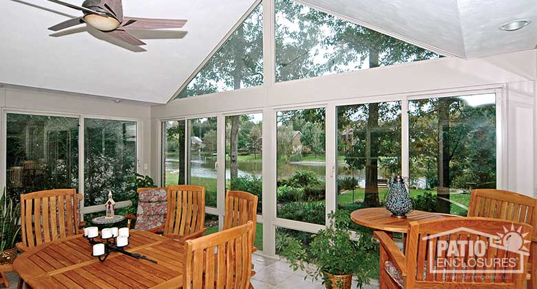White four season sunroom with aluminum frame, glass knee walls and gable roof.