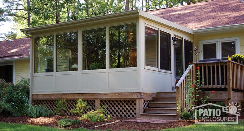 Sandstone four season sunroom with vinyl frame, solid knee wall and single-slope roof.