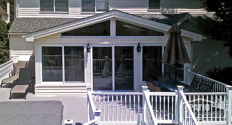 White four season sunroom with vinyl frame, solid knee wall and custom gable roof.