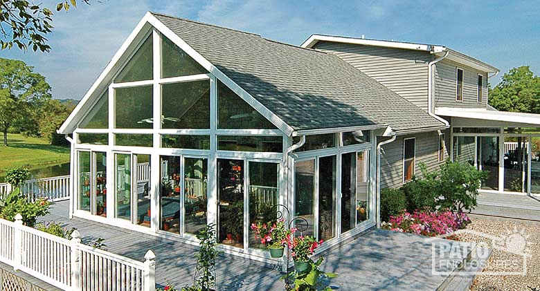 White four season sunroom with vinyl frame, transoms and shingled gable roof.