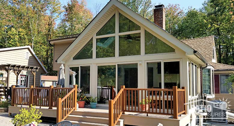Sandstone four season sunroom with vinyl frame, glass knee walls and shingled gable roof.