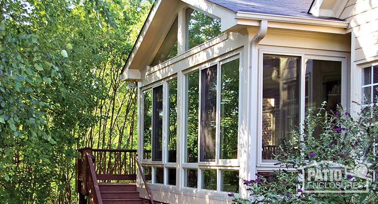 Sandstone four season sunroom with vinyl frame and glass knee walls enclosing an existing screened porch.