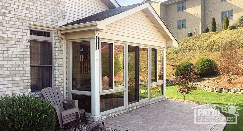 Sandstone four season sunroom with vinyl frame enclosing an existing covered patio.