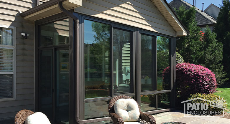 Bronze four season sunroom with aluminum frame enclosing an existing covered patio.
