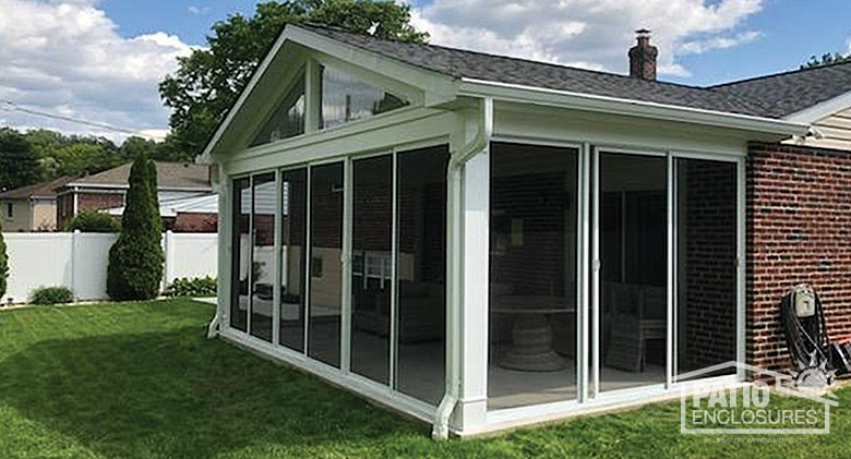 White screen room enclosing existing covered patio with gable roof.